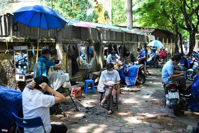 """Tại một góc phố Thái Thịnh hàng loạt """"đấng mày râu"""" ngồi chờ để được sử dụng dịch vụ trong ngày đầu Hà Nội mở lại các dịch vụ."""